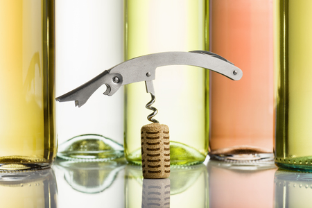 inserted: corkscrew inserted on cork with wine bottles on background Stock Photo