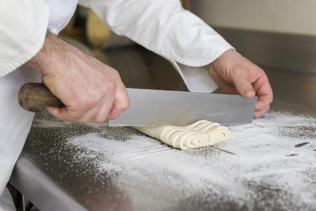 pasteles: pastelero corta la masa para preparar galletas de