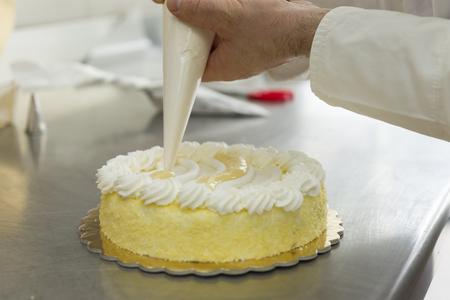 banketbakker garneren een taart met slagroom