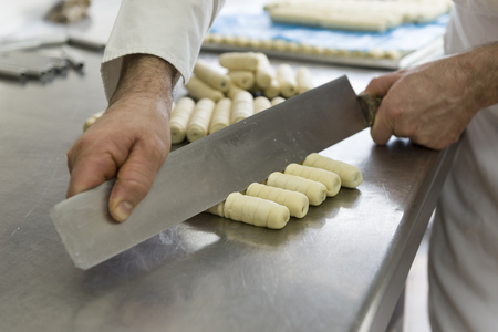 pastry chef: pastry chef cuts the dough for preparing cookies Stock Photo