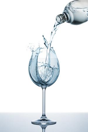 frescura: vertido de agua natural sobre el vidrio con salpicaduras Foto de archivo