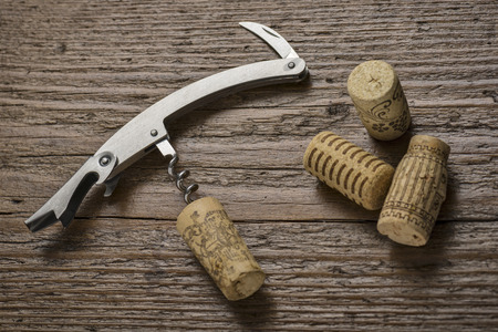 inserted: corkscrew with inserted cork on wooden table