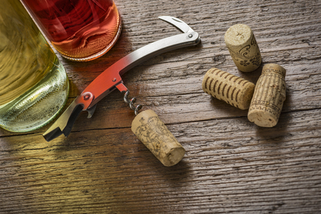 uncork: corkscrew with inserted cork and wine bottles on wooden table Stock Photo