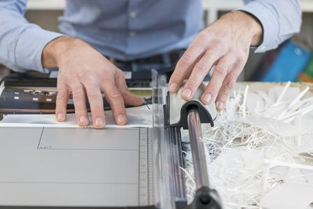 cutting machine is: man cutting print with precision cutter
