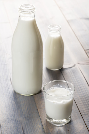 glass cup and bottle full of milk, on wooden table