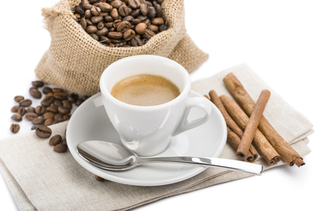 dispenser: cup of coffee on napkin with canvas bag full of coffee beans and cinnamon, on white background Stock Photo