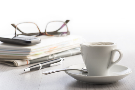 steaming cup of coffee on white office table with notes, phone, eyeglasses and ball pen on background.