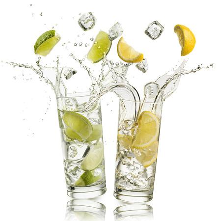 Vaso lleno de agua con rodajas de limón y limón y cubitos de hielo cayendo y salpicando agua, sobre fondo blanco Foto de archivo