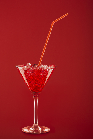 cocktail glass  , ice cubes and thin cane on red background.