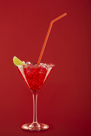cocktail glass  , lemon slice, ice cubes and thin cane on red background. Stock Photo