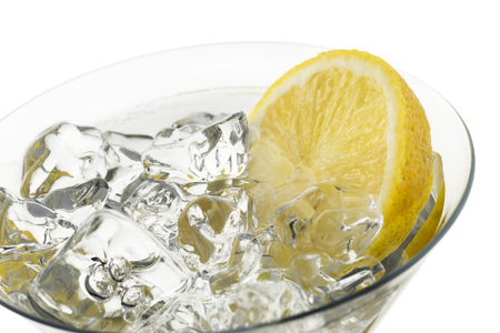 glass full of fresh water with lemon slices, on white background