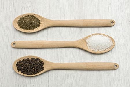 Cucchiai di legno con sale, pepe e origano sul tavolo. Archivio Fotografico - 92513106
