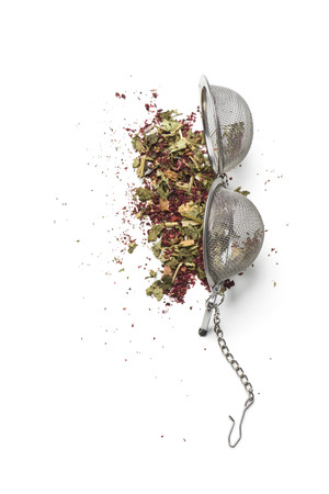 tea infuser opened on white table with herbal mixture for tea.