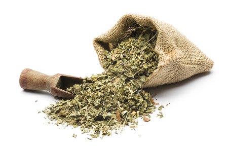 green tea mixture in juta bag with wooden scoop on white background