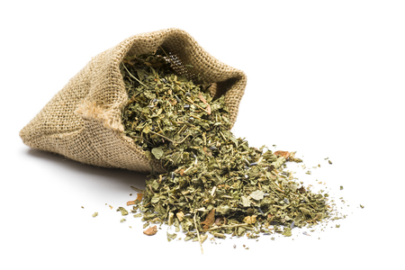 Mischung des grünen Tees in der Jutatasche auf weißem Hintergrund