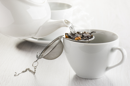 pouring hot water on tea infuser into white cup.