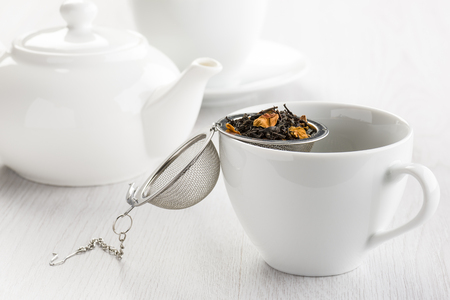 tea infuser opened on white cup with herbal mixture for tea. Stock Photo