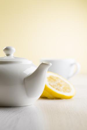 white teapot on table with lemon slices