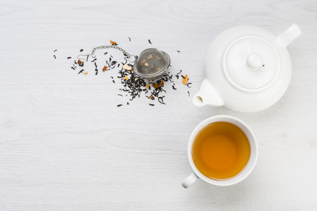 cup of tea with teapot and closed infuser with black tea on table Banque d'images