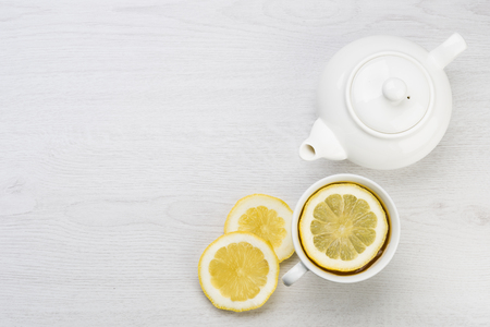 cup of tea with lemon slices and teapot on table