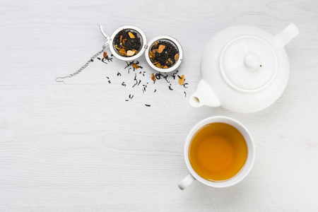 cup of tea with teapot and open infuser with black tea on table Stock Photo