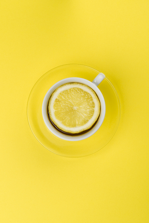 cup of tea with lemon slice on yellow tablecloth Stock Photo