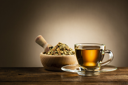 glass cup of tea with herbal tea on wooden table