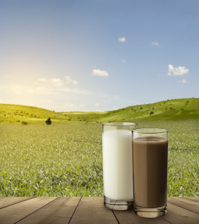 two glasses with milk and chocolate on wooden table with background landscape Archivio Fotografico