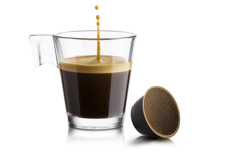 Black coffee in glass cup with coffee waffle and jumping drop on white background