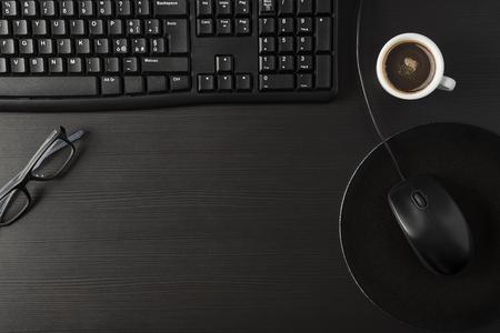 Total black desk with desktop and cup of coffee Archivio Fotografico