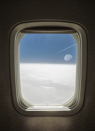 plane flying above the clouds with moon, seen from window airplane.