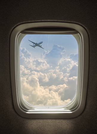 plane flying above the clouds, seen from window airplane. Stock Photo