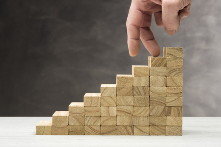 Concept of decrease. Graphic with wooden steps on grey background with hand coming down.