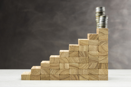 Concept of growth. Graphic with wooden steps on grey background with stack of coins on top.