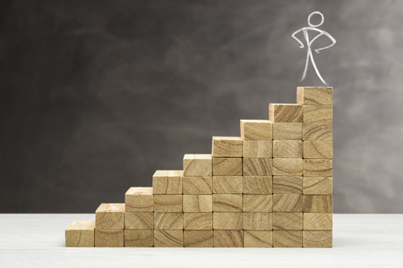 Concept of growth. Graphic with wooden steps on grey background, with human shape on top. Imagens - 122716066