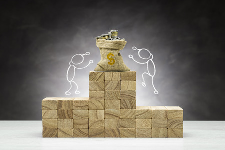 Concept of competition. Wooden podium on grey background with bag full of coins and people shapes. Imagens