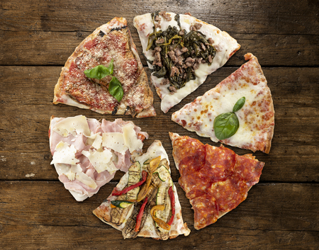 Variety of sliced pizza on wooden table