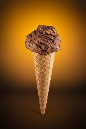 Chocolate ice cream cone on brown background