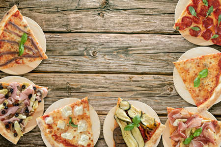 Top view of pizza slices variety on wooden cutting boards