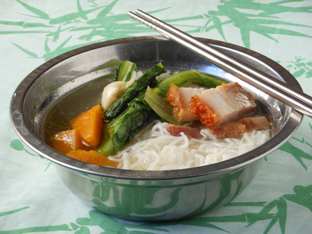 hoon: Chinese Mifen noodles soup with roast pork, lettuce and pumpkin. Stock Photo