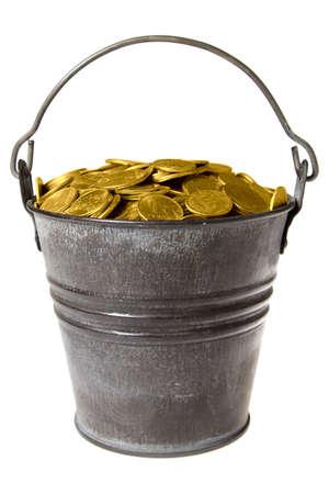 Old zinc bucket with golden coins. Isolated. Ñòàðîå öèíêîâîå âåäðî ñ çîëîòûìè ìîíåòàìè. Îáòðàâëåíî. photo