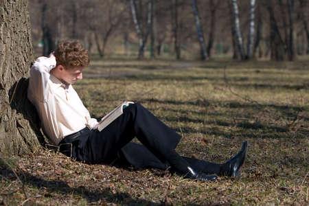 hombre estudiando: Joven estudio de libro en la universidad de traspatio.