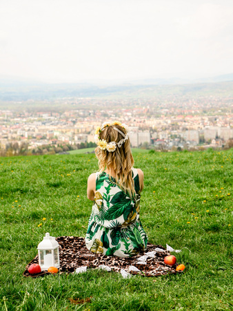 The girl sitting on the mountain,looking at the whole city