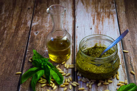 preparation of Genoese pesto, the sauce ready in the glass jar, pine nuts, olive oil and basil leaves