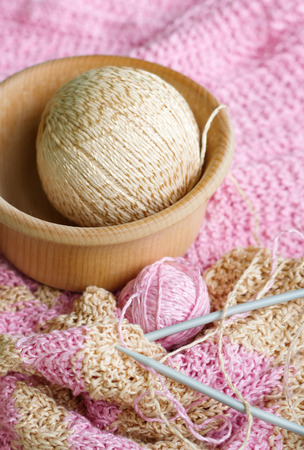 neckwear: Striped lovely knitted scarf, knitting needles and two balls of yarn on a white table. Balls of yarn lying in a wooden bowl. Yarn is pink and beige.