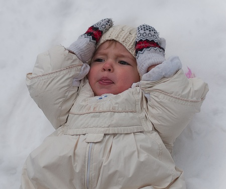 Little girl lays on snow photo