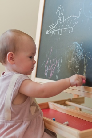 Little girl paints on the board photo