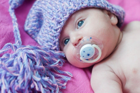 soother: Little baby with soother in hat lays Stock Photo