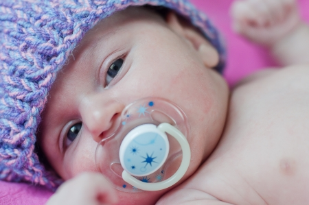 Little baby with soother in hat lays photo