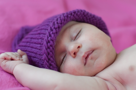 Little baby in hat sleeps peacefully photo